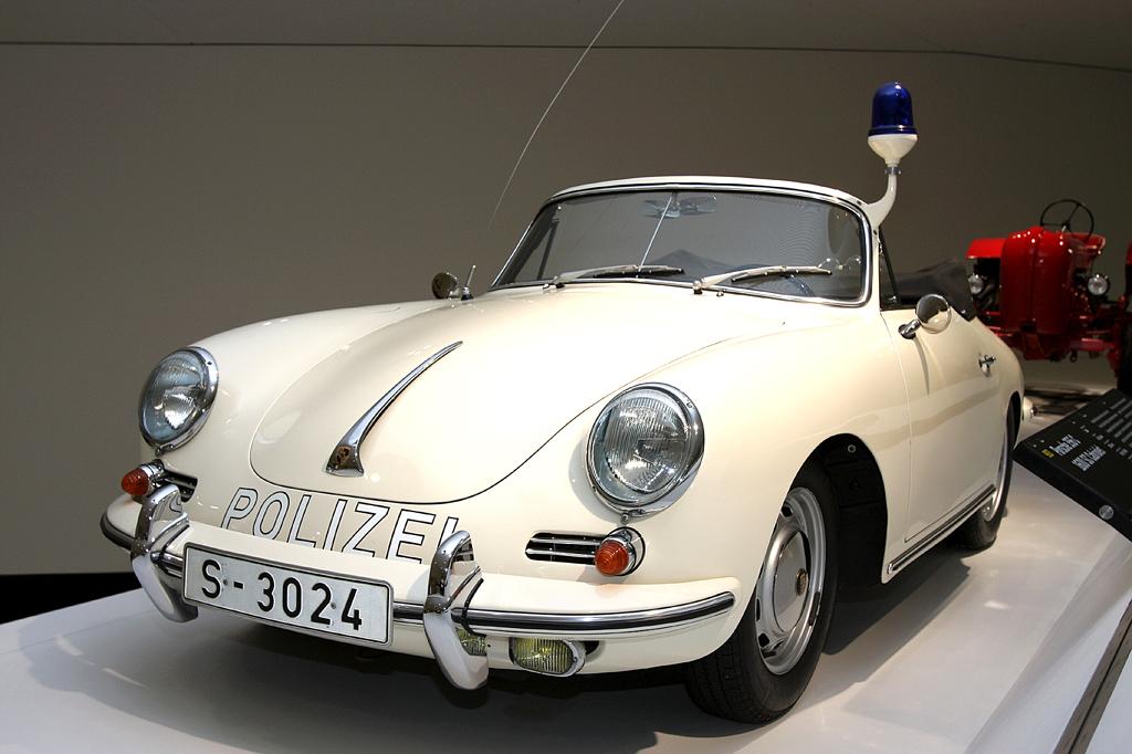 Ganz in Weiß: Polizei-Porsche, dahinter ein roter Porsche-Traktor.