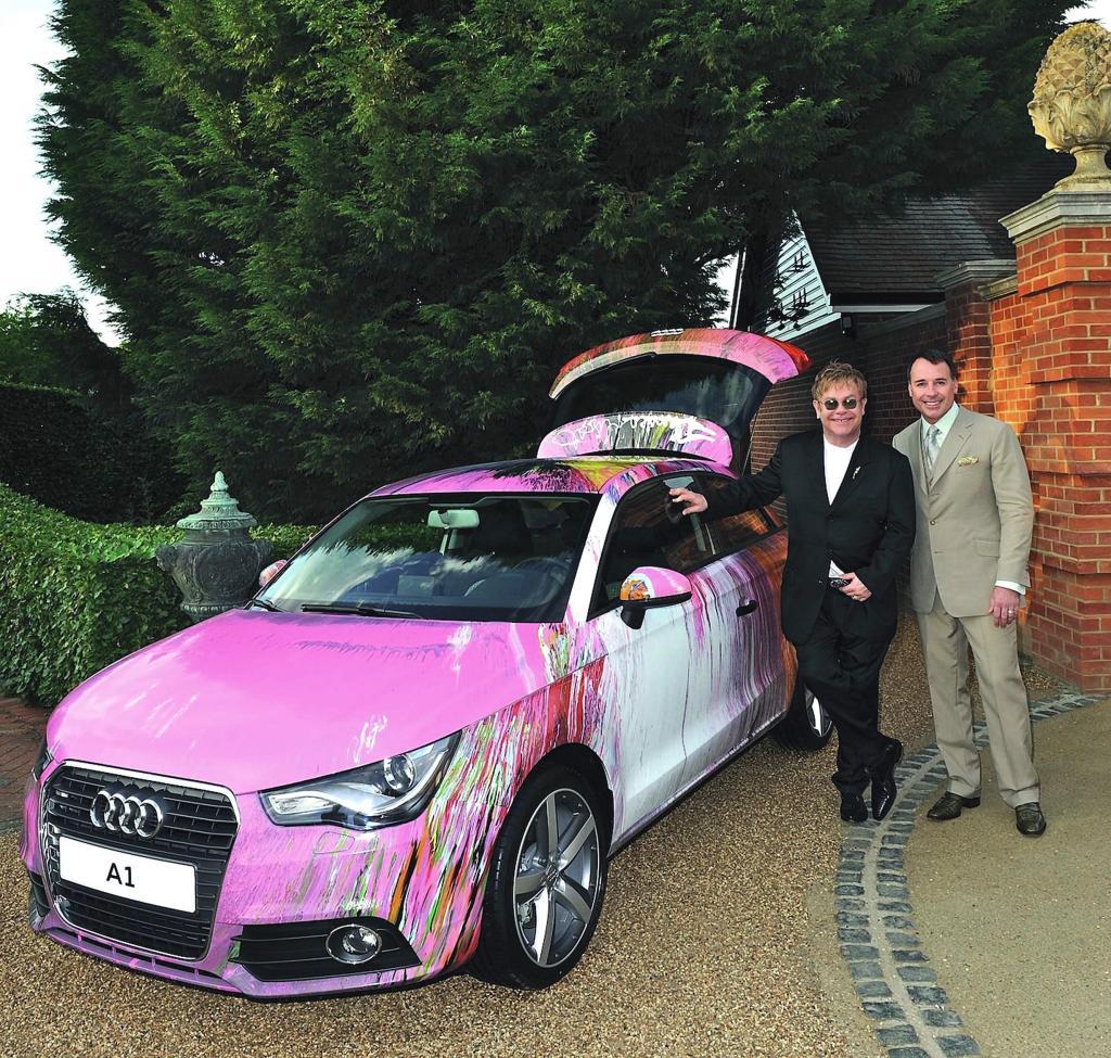 Elton John mit Ehepartner David Furnish vor dem von Hirst extravagant gestalteten A1.