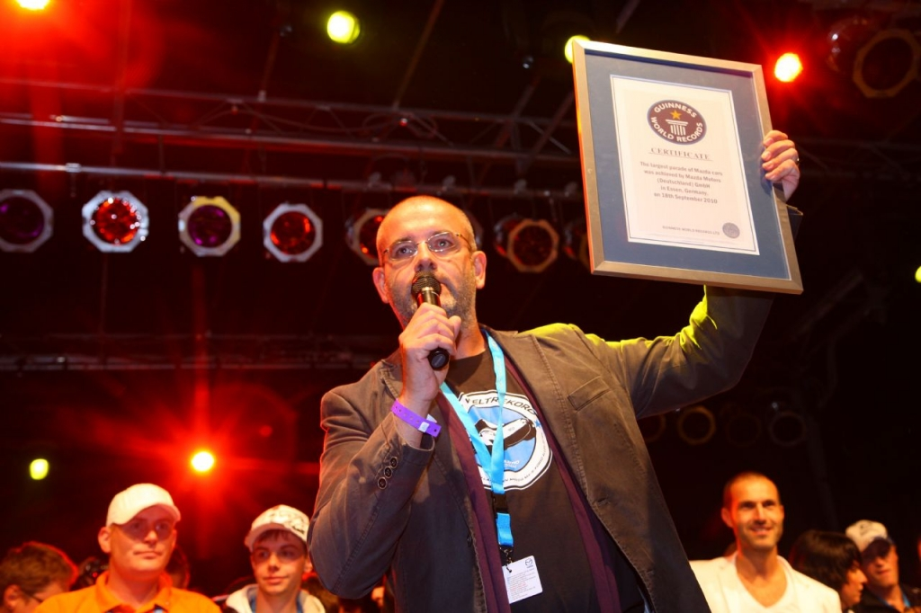 Marketing-Direktor Dino Damiano mit der Guinness Urkunde zum längsten MX-5 Korso der Welt