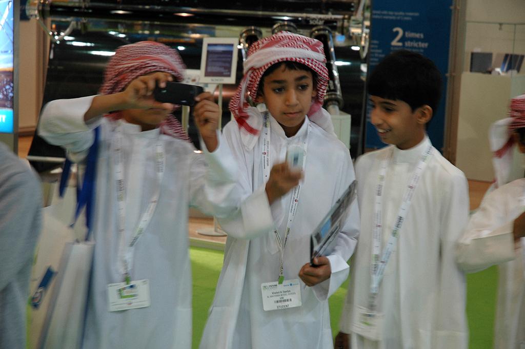 Junge Emiratis beim Fotografieren der Daimler-Ausstellungsexponate.