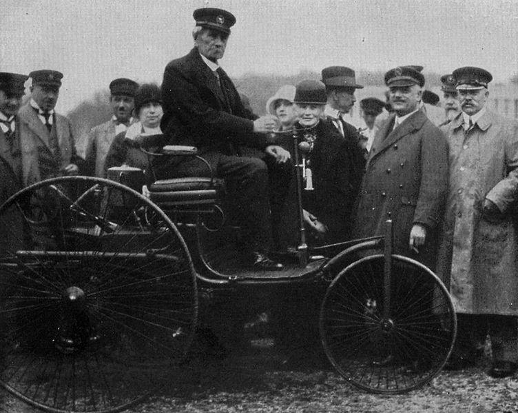 Carl Benz thront auf seiner Erfindung