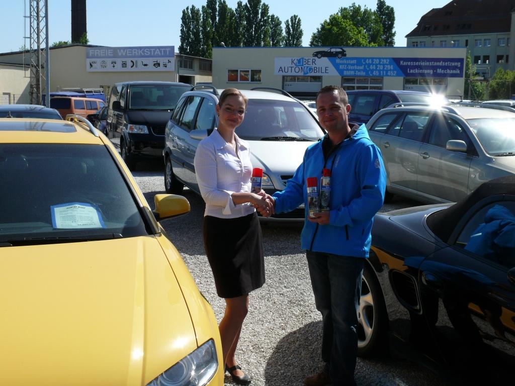 Händlertipp: Gekonnt in Szene setzen - Ein Tipp von Autoservice Klie & Bernard GbR - auto.de-Händlerbetreuer André Wolf übergibt Silva Mosig ein Nigrin Pflegeset