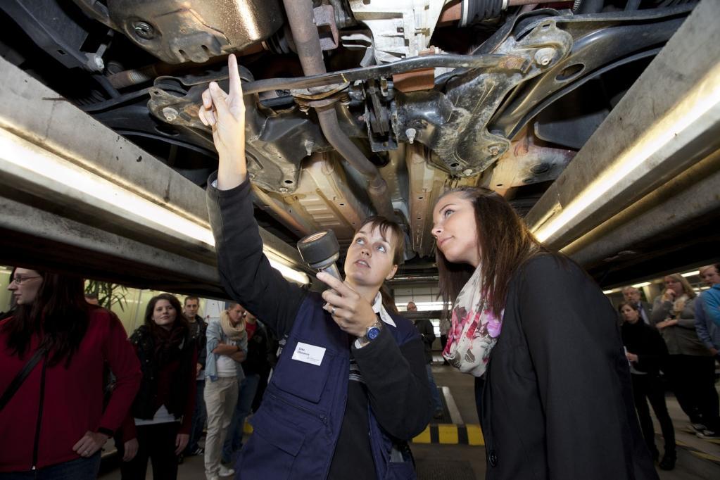 Auszubildende und Prüferin des TÜV Rheinland überprüfen beim kostenlosen Profi-Check sicherheitsrelevante Bauteile des Fahrzeugs.