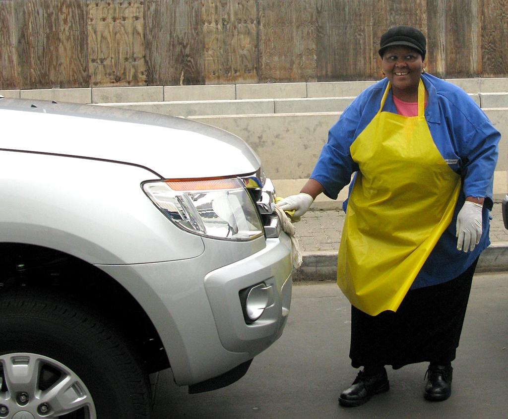 Eine Arbeiterin wischt die Front eines Rangers-Pickups trocken.