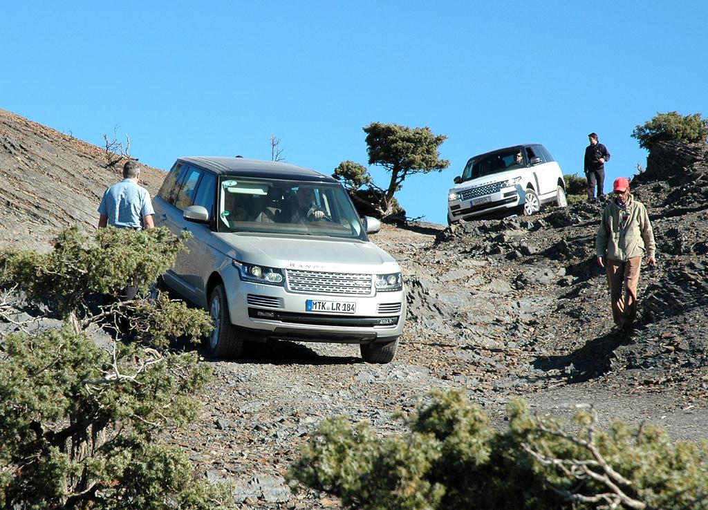 Langsam bewegen sich zwei Range Rover einen steilen Abhang hinunter.