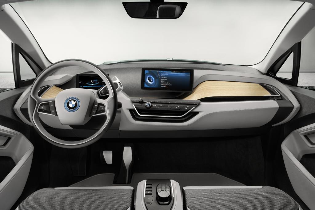 Auch innen hat der neue i3 große Ähnlichkeit mit dem Coupé-Konzept, Zwei Bildschirme, einer direkt vor dem Fahrer und einer in der Mitte, informieren den Fahrer, offenporiges Holz auf den Oberflächen schmeichelt der Hand