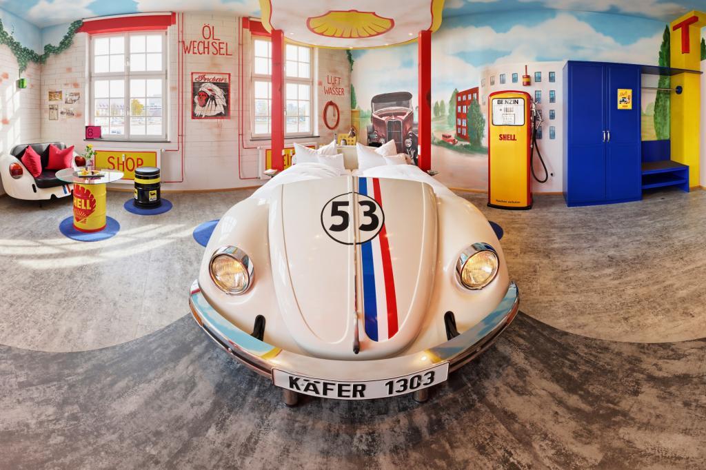 Die Tankstellen-Suite mit Herbie-Bett, Zapfsäulen und Neon-Licht.
