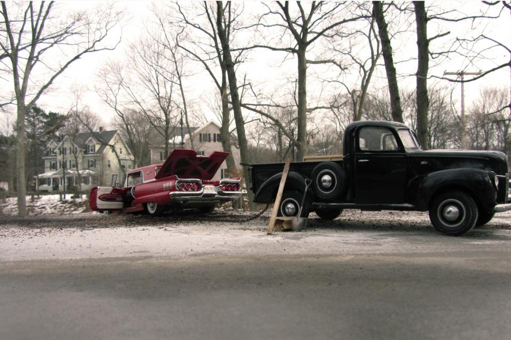 Ein schwarzer Pick-up zieht einen pinken Ford Thunderbird aus dem verschneiten Straßengraben - der Schnee ist übrigens Back-Natron