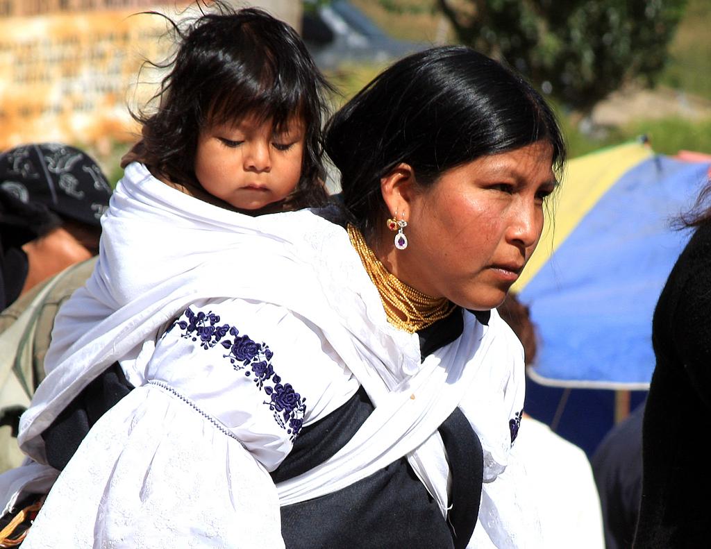 Eine Indiomutter mit ihrem Kind auf dem Viermarkt in Otavalo.