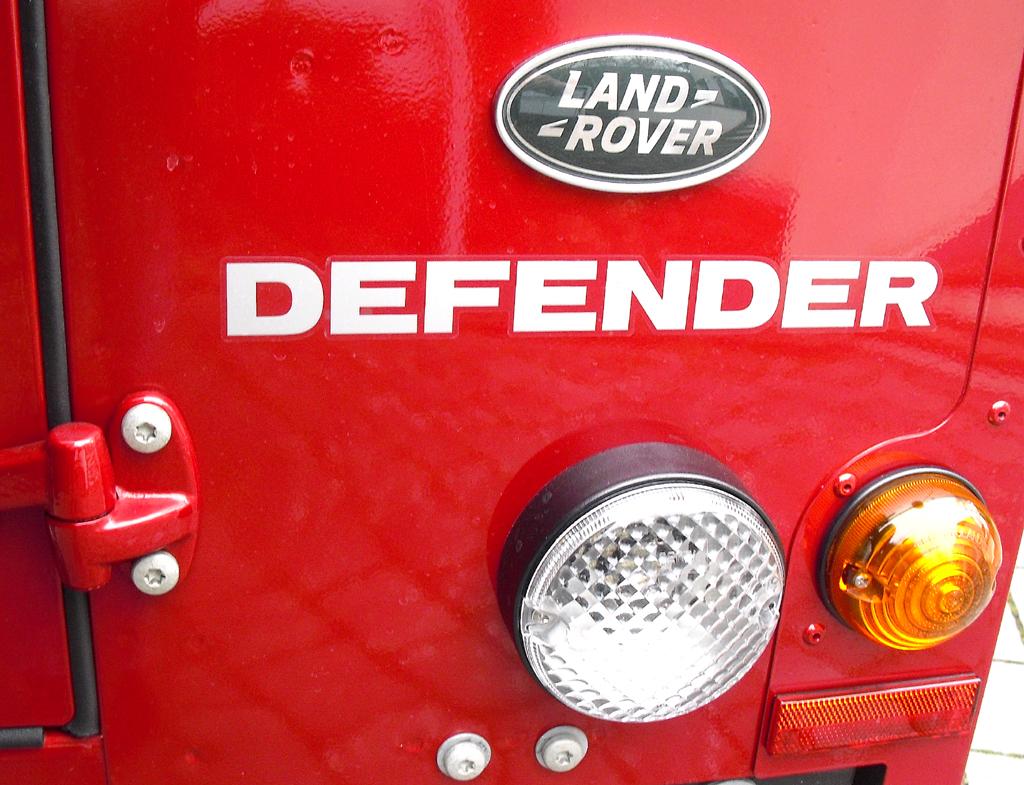 Land Rover Defender: Markenlogo, Modellschriftzug und Leuchteinheit am Heck.