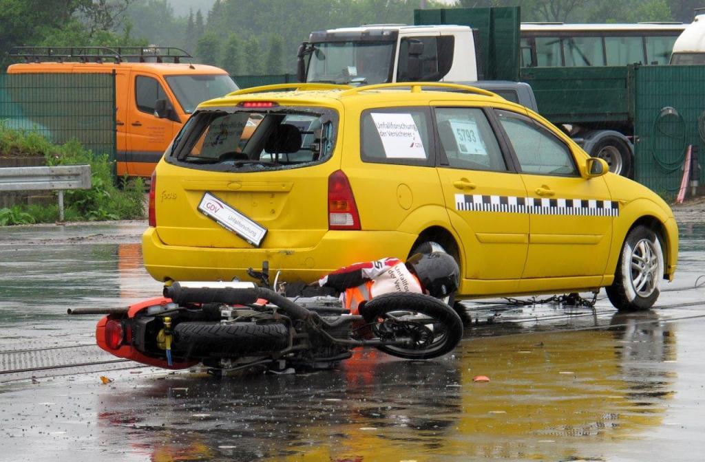 Das Motorrad liegt ein Stück hinter dem gelben Kombi auf der linken Seite, der Dummy ist vom Auto wieder abgeglitten und liegt verkrümmt direkt hinter dem Fahrzeug