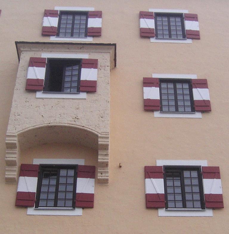 Mit rot-weiß gestreiften Fensterläden: Hausfassade von Schloss Fuschl.