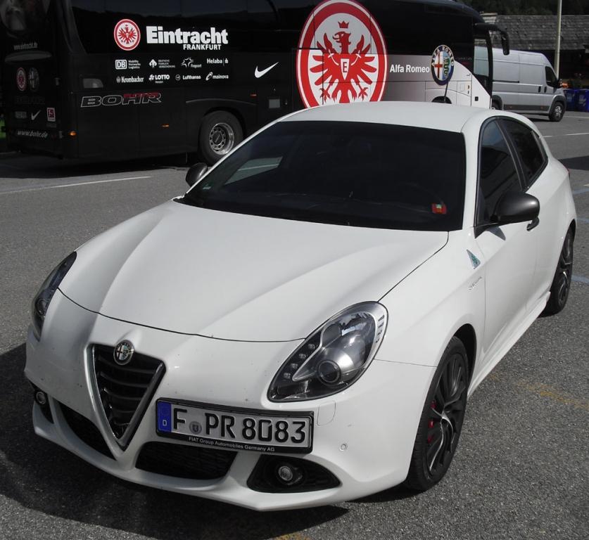 Alfa-Romeo-Giulietta als Quadrifoglio Verde vor Eintracht-Frankfurt-Bus.