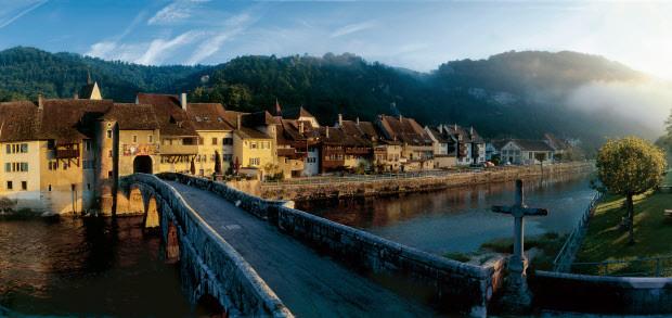 Mit der spaetromanischen Stiftskirche, den schmucken Haeusern und der alten Steinbruecke gilt St-Ursanne am Doubs als 'Perle des Jura'.